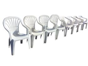 A set of four plastic garden armchairs with arched backs & flared splats; and two other similar