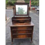 A George VI oak dressing table, the bevelled mirror in egg & dart moulded frame supported on twisted