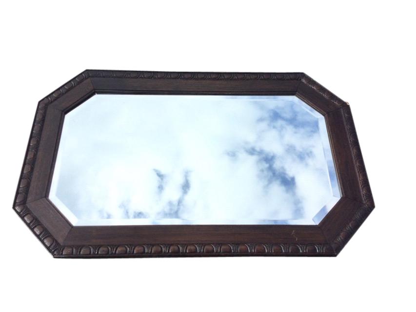 A George VI oak framed rectangular mirror, the bevelled plate in egg & dart carved octagonal