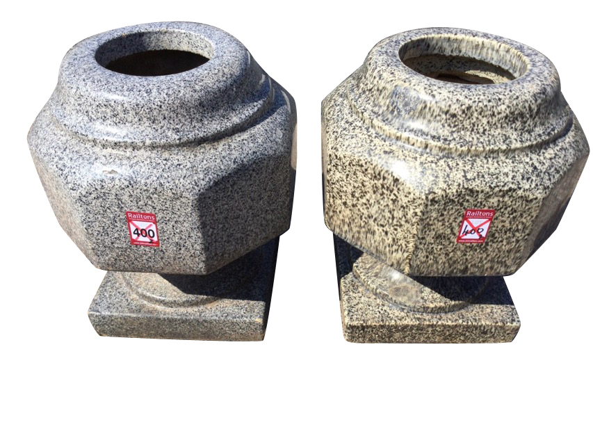 A matched pair of stoneware granite glazed octagonal urns with moulded rims, raised on square plinth