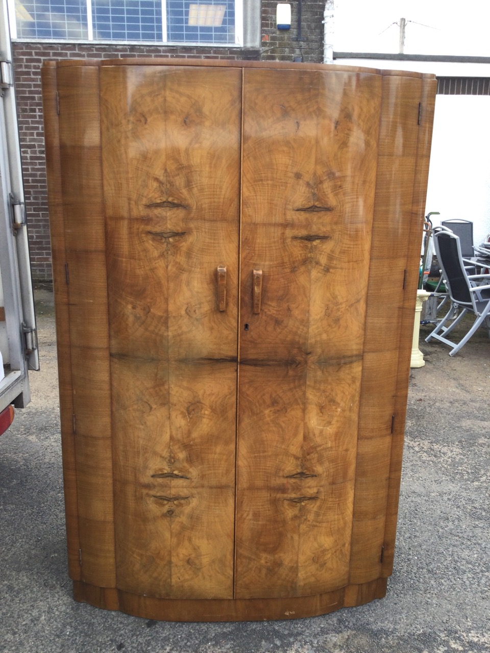 A deco walnut wardrobe of scalloped bowfronted outline having two doors enclosing an interior with - Image 2 of 3