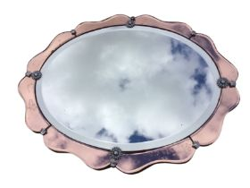 An oval 1950s mirror with bevelled plate, having chrome flowerhead mounts within a pink bevelled
