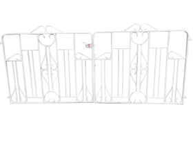 A pair of painted wrought iron driveway gates, the rounded frames with vertical bars and scrolled