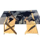 A rectangular contemporary plate glass dining table, the top silhouette printed with a world map,