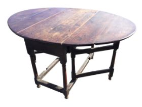 An eighteenth century oval oak gateleg dining table, the top with drop-leaves above a frieze with