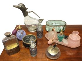 A glass claret jug in the form of a duck with silver plated mounts; a faceted glass flask with