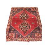 An oriental rug woven with two octagonal hooked medallions on red field having charcoal grey