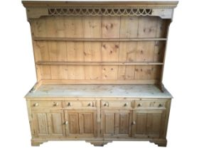 A pine dresser, the delft rack with moulded dentil cornice above a pierced fretwork apron, having