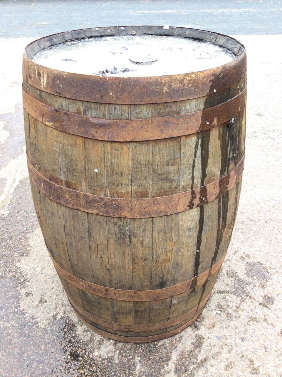 An oak whiskey barrel, the staves bound by six metal riveted strap bands. (34in)