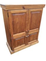 A pine cupboard with moulded cornice above four fielded panelled knobbed doors enclosing shelves,
