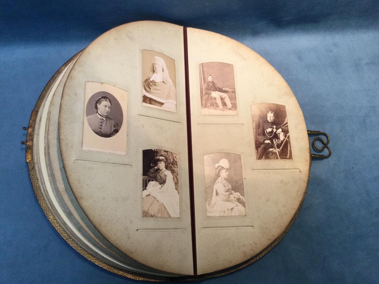 A Victorian leather bound crescent shaped album of studio portrait photographs, the sitters