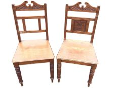 A pair of late Victorian oak chairs with pediment carved back rails above carved vase of flowers
