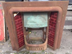 A late Victorian cast iron fire insert, the cushion moulded frame with shell embossed corners fitted