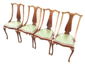 A set of four leather upholstered mahogany dining chairs, the backs inlaid with boxwood stringing