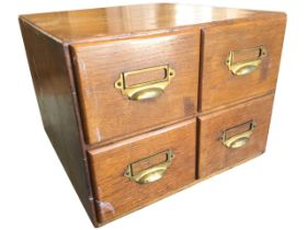An Edwardian oak card index cabinet, with four drawers mounted with brass cup handles and label-