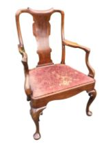 A nineteenth century Queen Anne style walnut armchair with wide shaped splat beneath a scroll carved