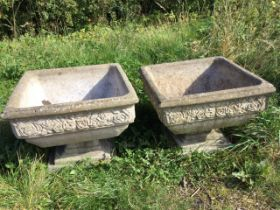 A pair of square composition stone urns with moulded rims above floral embossed friezes, raised on