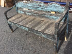 A painted bench seat with shaped moulded back and downswept arms framing a plank seat, raised on