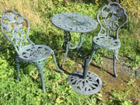 A rose embossed garden table, sunshade stand and pair of chairs, the verdigris patinated pieces with