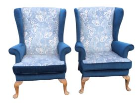 A pair of velour upholstered wingback armchairs with flared arms above loose cushions on sprung