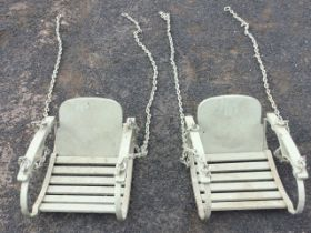 A pair of painted swinging childs chairs with rounded backs and slatted seats, the arms supported by