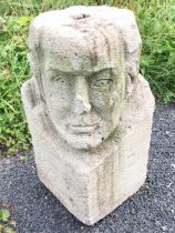 A square block carved with a man's head to corner, with hole to top. (18in)