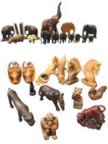 A collection of carved and moulded animals including a set of graduated elephants, horses, dolphins,
