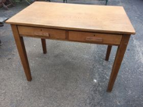 A George VI oak writing desk with rectangular top above two frieze drawers, raised on square