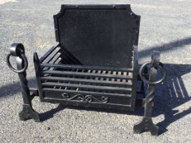 An C18th style cast iron firegrate, with panelled fireback and basket grate supported on fire dogs