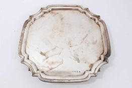 Silver salver of square form, with shaped corners on four bun feet (Sheffield 1933) by Viner's Ltd.