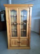 Contemporary stained pine bookcase with two leaded glazed doors above enclosing three fixed shelves