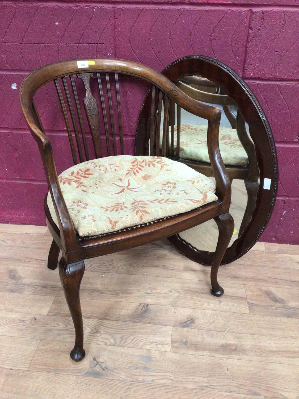 Edwardian mahogany tub chair with caned seat and a mahogany framed oval wall mirror (2)