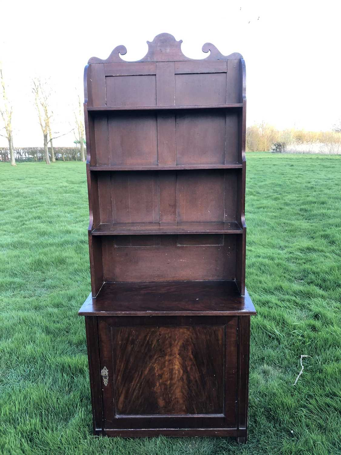 19th century mahogany and grained waterfall bookcase with scrolling top rail and graduated open shel