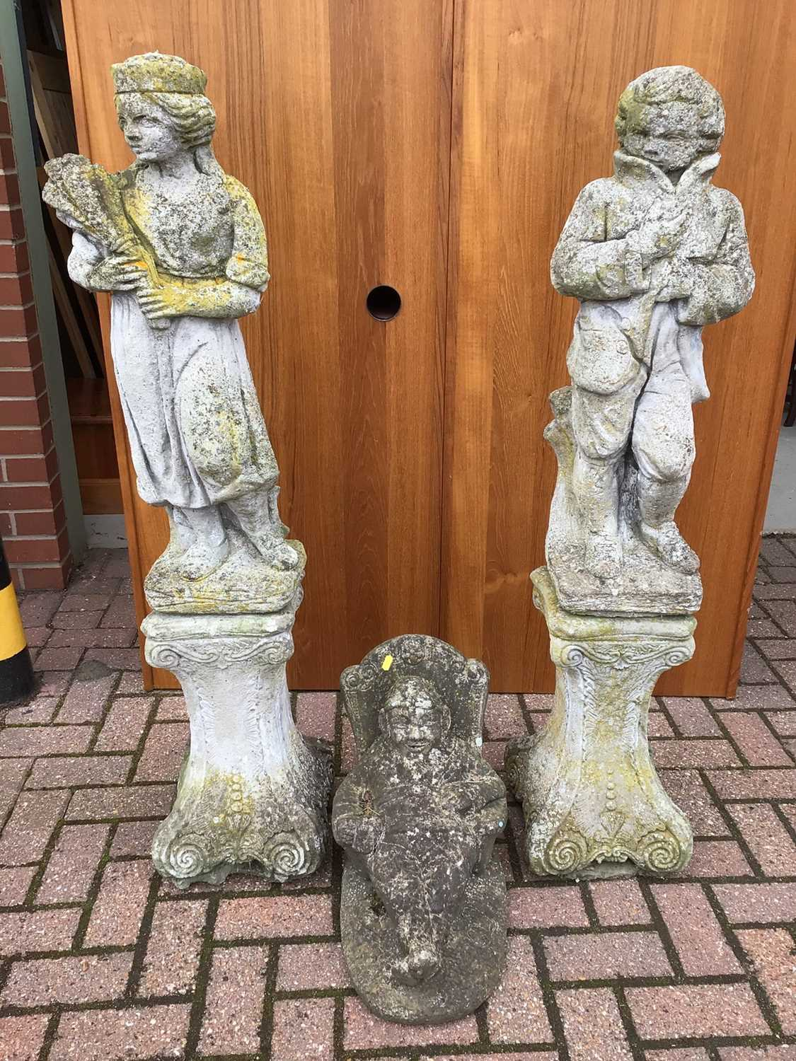Pair of concrete figures on stands 126cm and 123cm and one other of a seated gnome 40cm