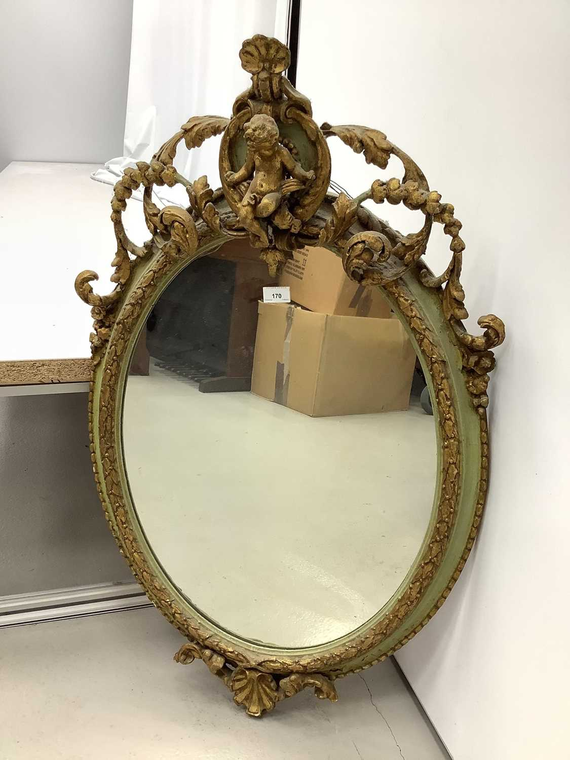 Oval wall mirror in green and gilt frame with cherub mount, 100cm x 61cm