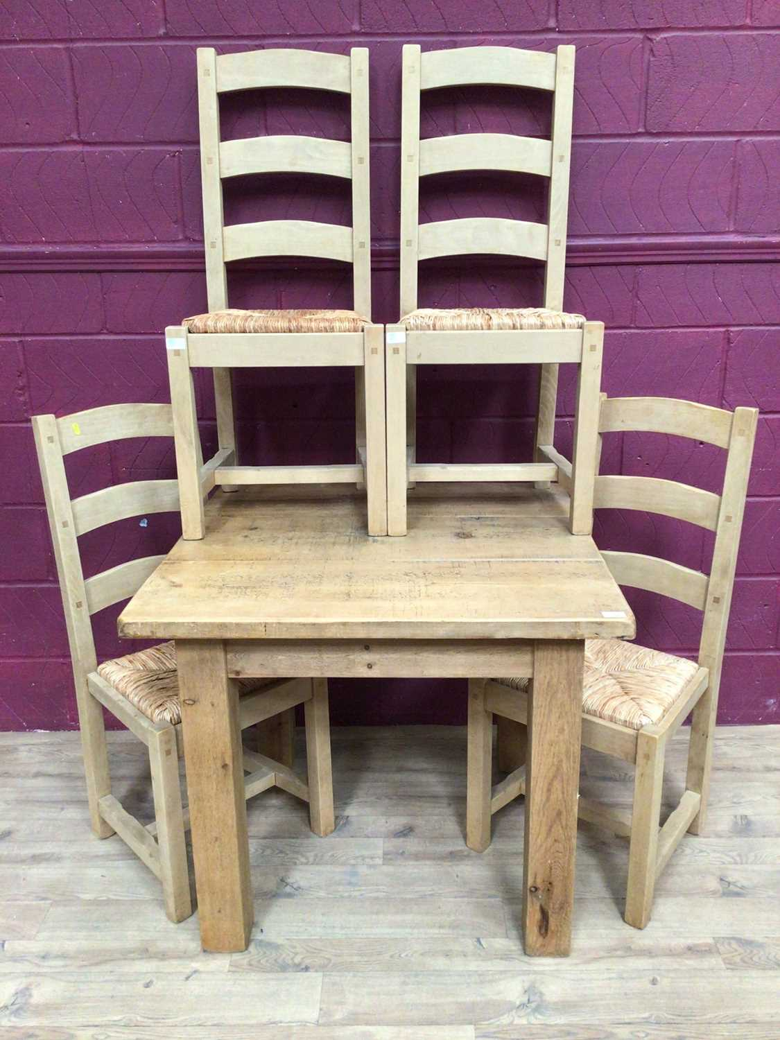 Contemporary light oak dining table and four matching ladder back chairs with rush seats