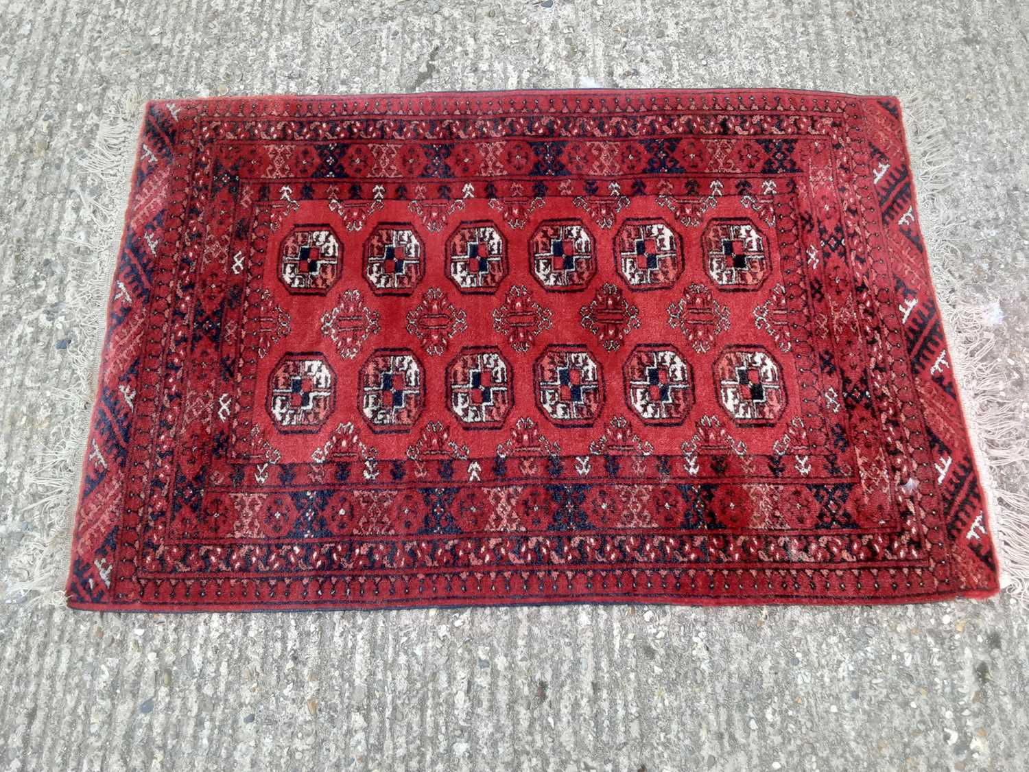 Eastern rug with geometric decoration on red ground, 120cm x 82cm