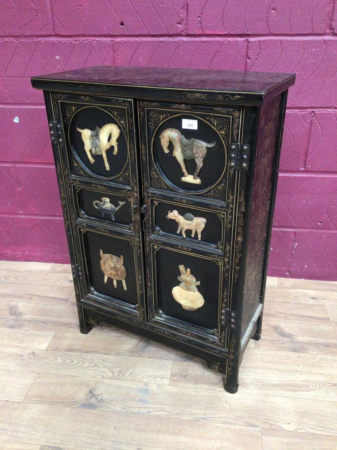 Oriental lacquered two door cupboard decorated with applied Oriental plaques, 61cm wide, 29.5cm deep