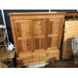 Modern pine triple wardrobe wiht three panelled doors, three short and two long drawers below, 184cm