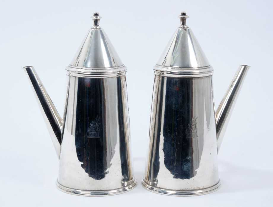 Pair George V silver cafe au lait pots of tapering cylindrical form, with engraved armorial crests,