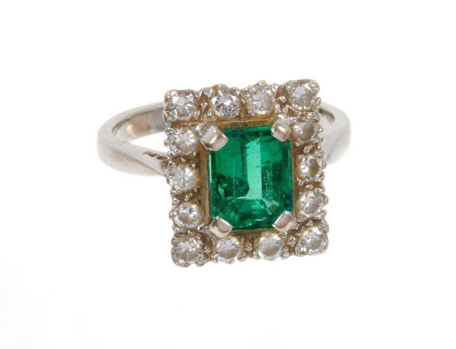 Emerald and diamond cluster ring with a rectangular step cut emerald surrounded by a border of fourt