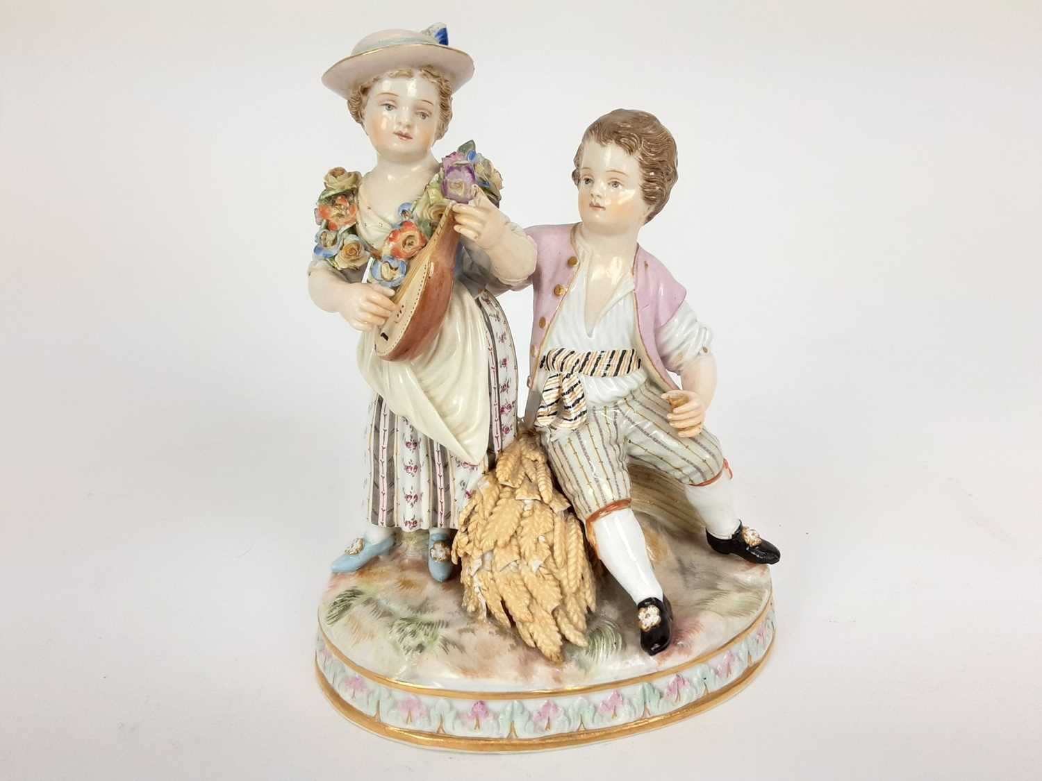 Meissen porcelain group, late 19th century, the boy sat on a sheaf of wheat, listening to a girl pla