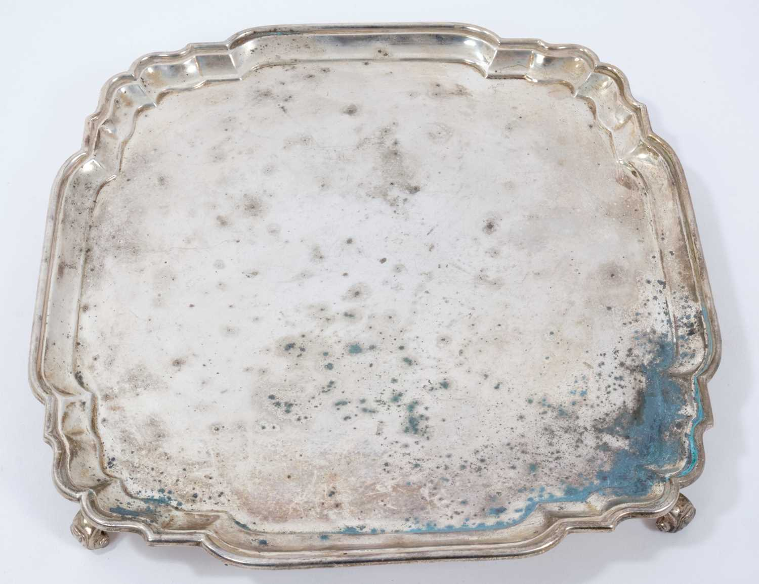 George V silver salver of shaped square form with piecrust border, on four leaf scroll feet