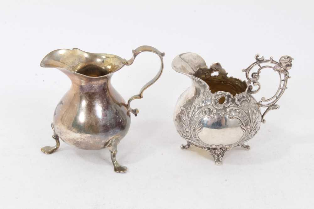 Victorian silver cream jug of baluster form, with scroll handle, on three paw feet