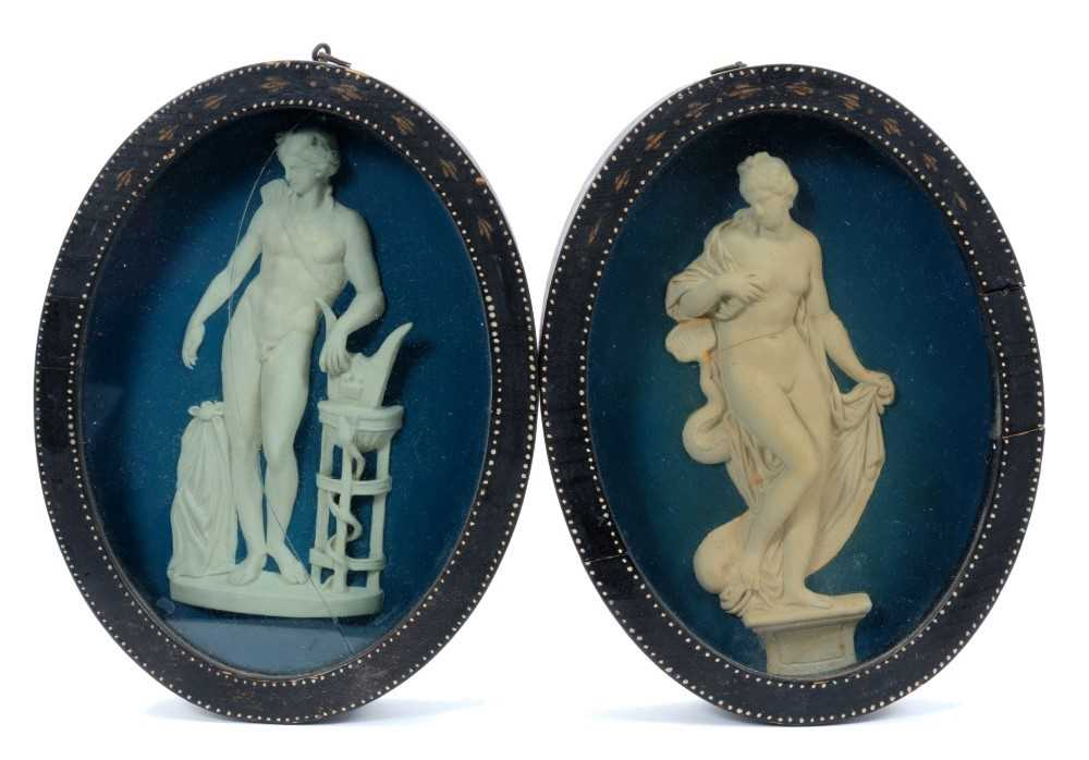 Pair of late 18th/early 19th century composition oval relief plaques depicting classical figures, in