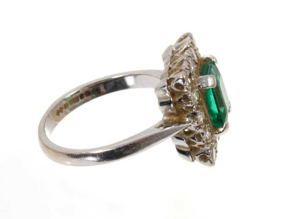 Emerald and diamond cluster ring with a rectangular step cut emerald surrounded by a border of fourt - Image 2 of 3