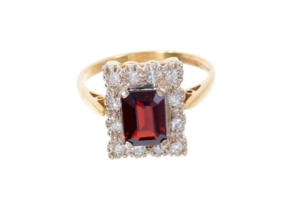Garnet and diamond cluster ring with a rectangular step cut garnet surrounded by a border of single