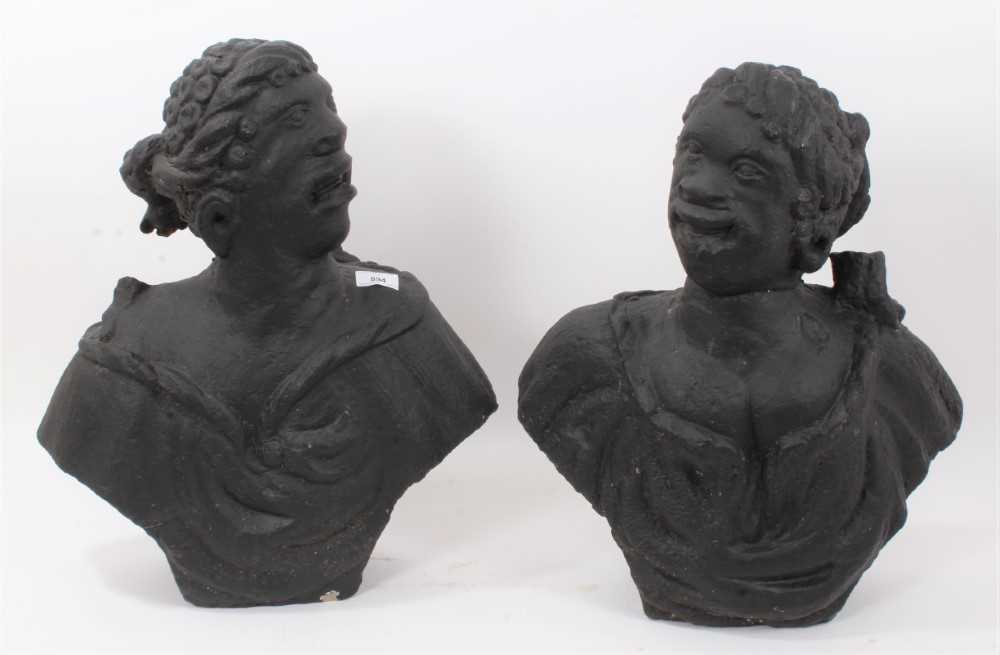 Rare pair of early carved stone niche busts of an African man and woman, pierced to underside of bas