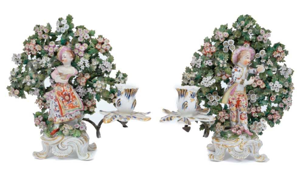 Pair of Bow 'New Dancer' figure candlesticks, circa 1765, with bocage decoration behind each figure,