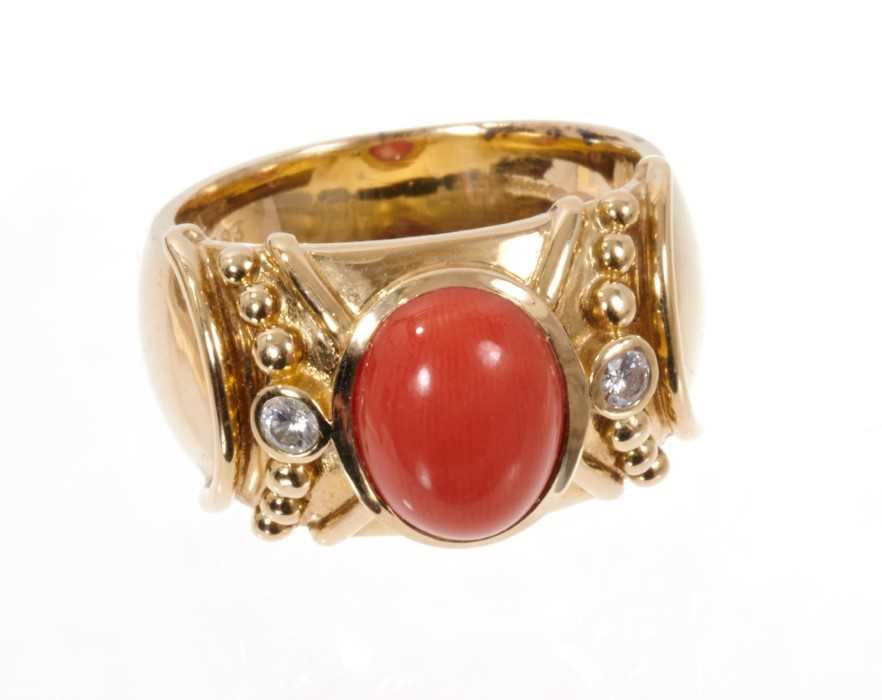 Coral and diamond dress ring, the wide 14ct yellow gold band with a central oval coral cabochon flan